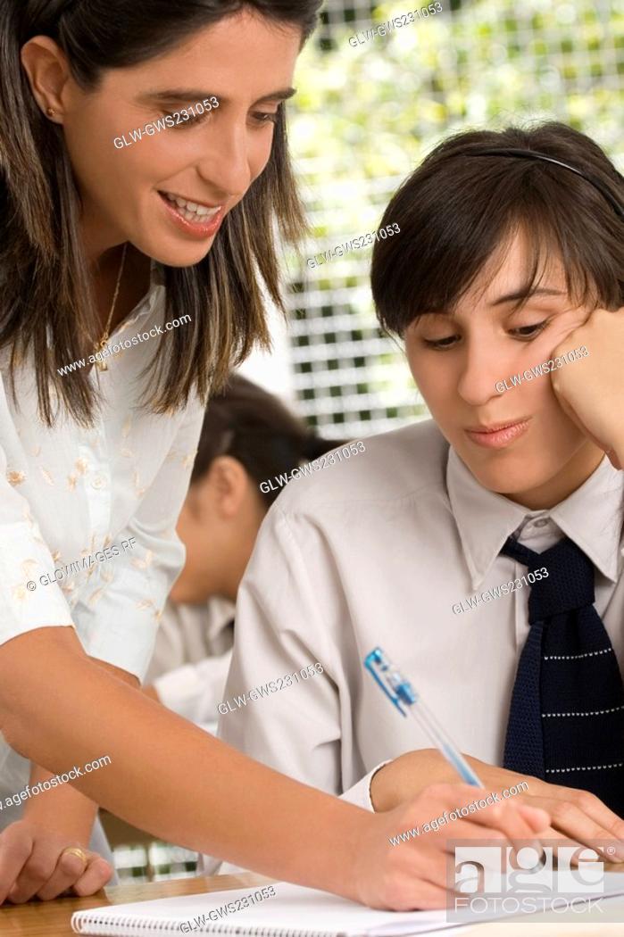 Stock Photo: Close-up of a female teacher teaching a teenage girl in a classroom.