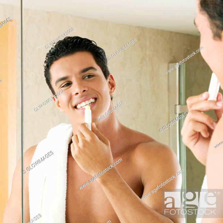 Stock Photo: Close-up of a young man applying lip balm.
