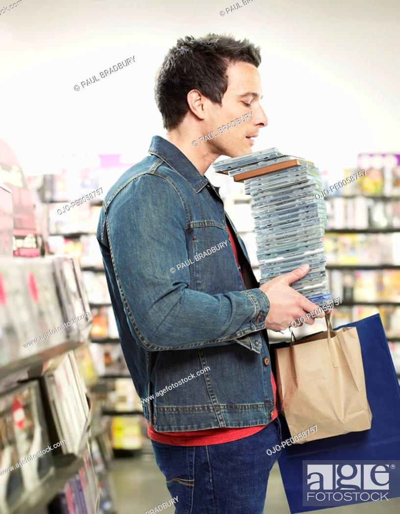 Stock Photo: Man carrying stack of CDs in store.