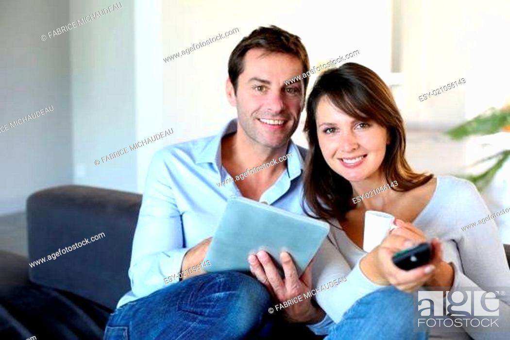 Photo de stock: Couple sitting in couch choosing tv program.