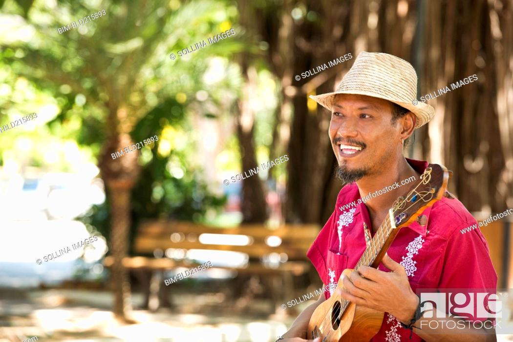 Imagen: Hispanic musician playing ukulele in park.