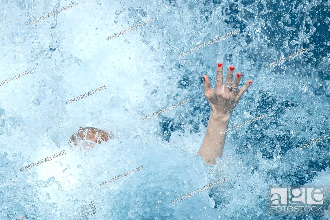Stock Photo: 07 August 2020, Baden-Wuerttemberg, Stuttgart: A woman dives into the pool in the Inselbad. Photo: Sebastian Gollnow/dpa.
