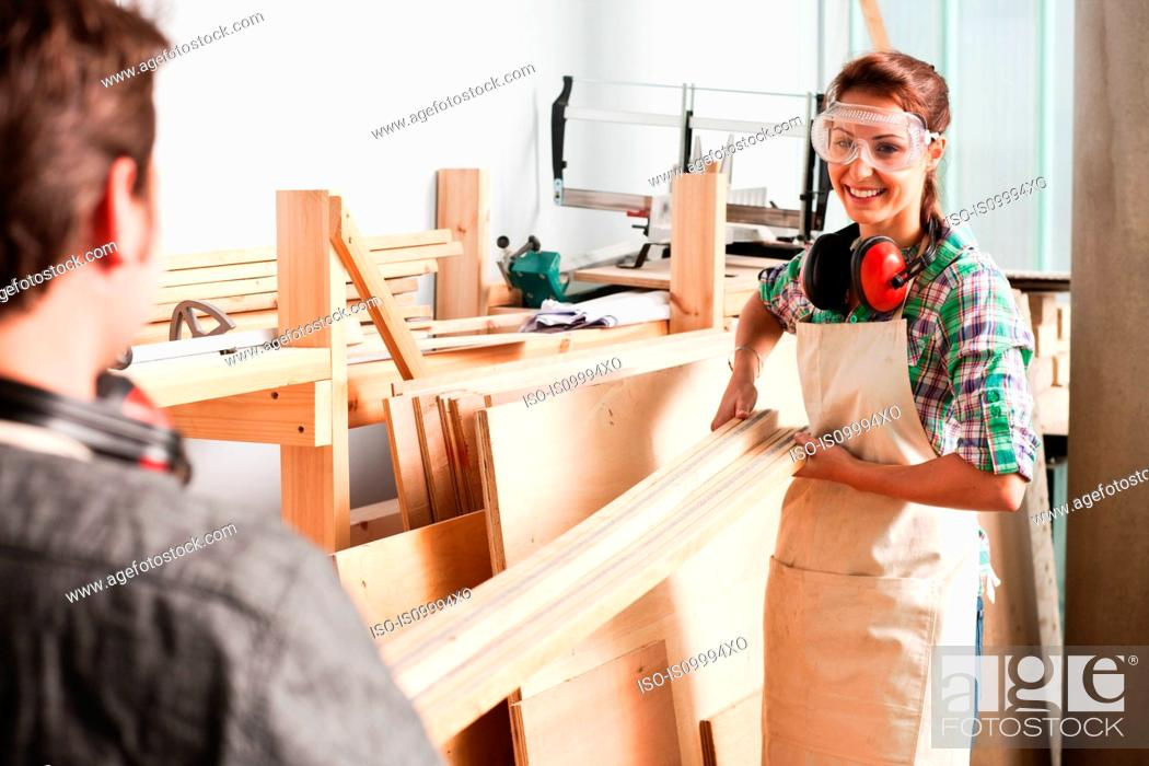 Stock Photo: Carpenters carrying wood in workshop.