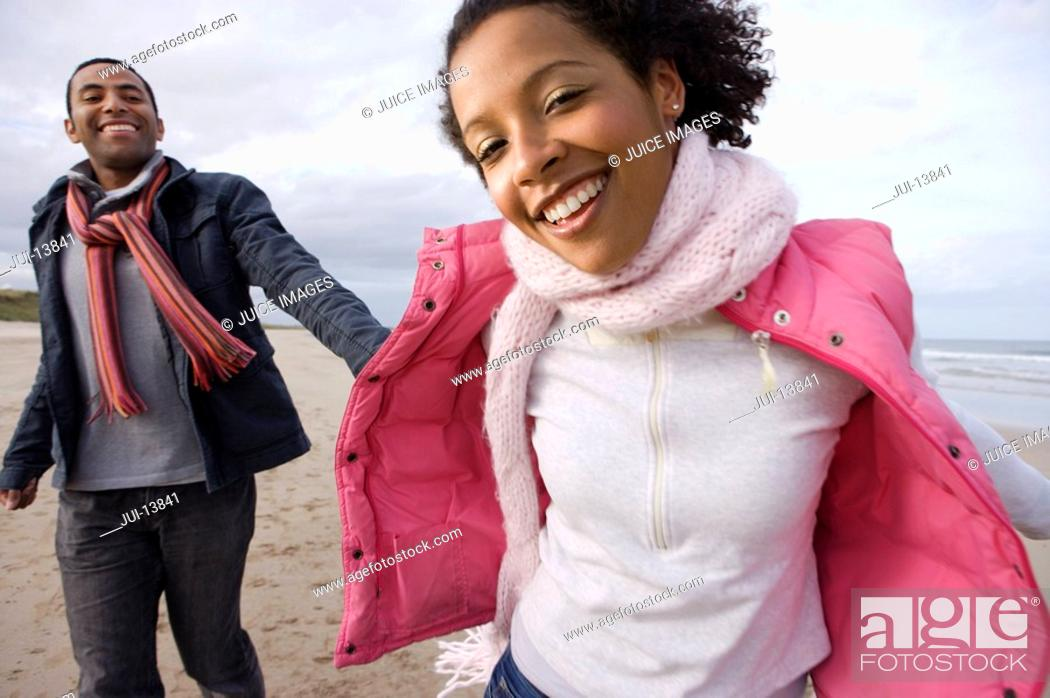 Stock Photo: Young couple hand in hand on beach, portrait of woman smiling.