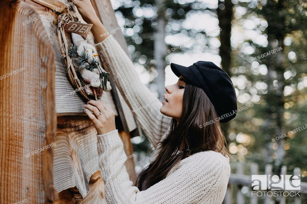 Stock Photo: Young woman decorating wooden house with Christmas decoration.