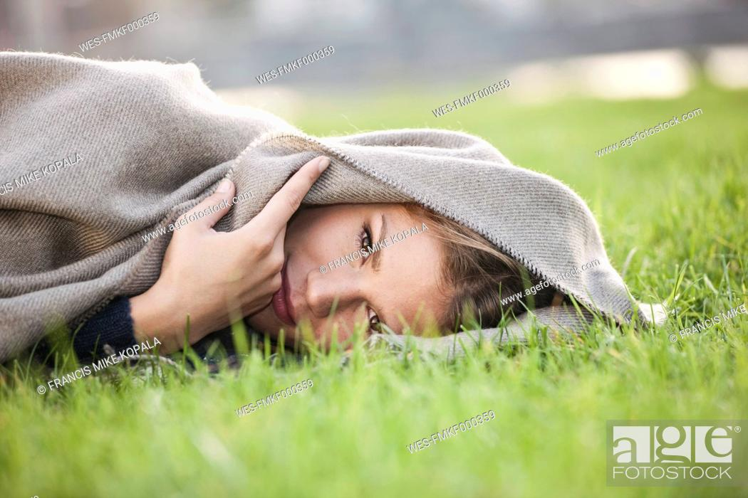 Stock Photo: Germany, Cologne, Young woman lying in grass, portrait.