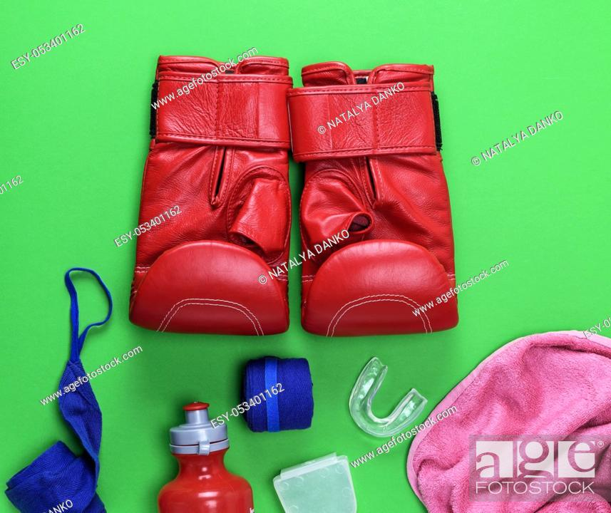 Stock Photo: red leather boxing gloves, a plastic water bottle and a pink towel and blue textile bandage on a green background.
