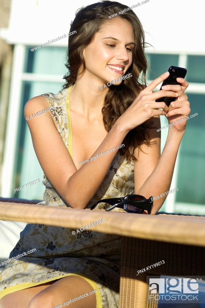 Stock Photo: Woman text messaging and smiling.