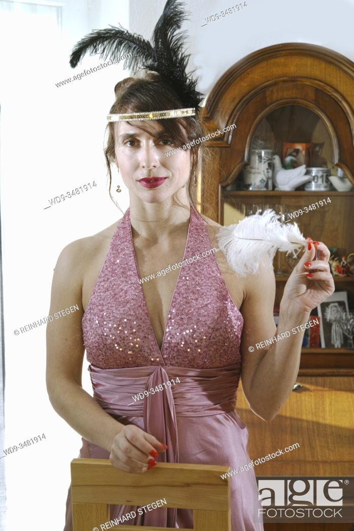 Stock Photo: 1920 fashion style dressed up young woman, feather in hair.