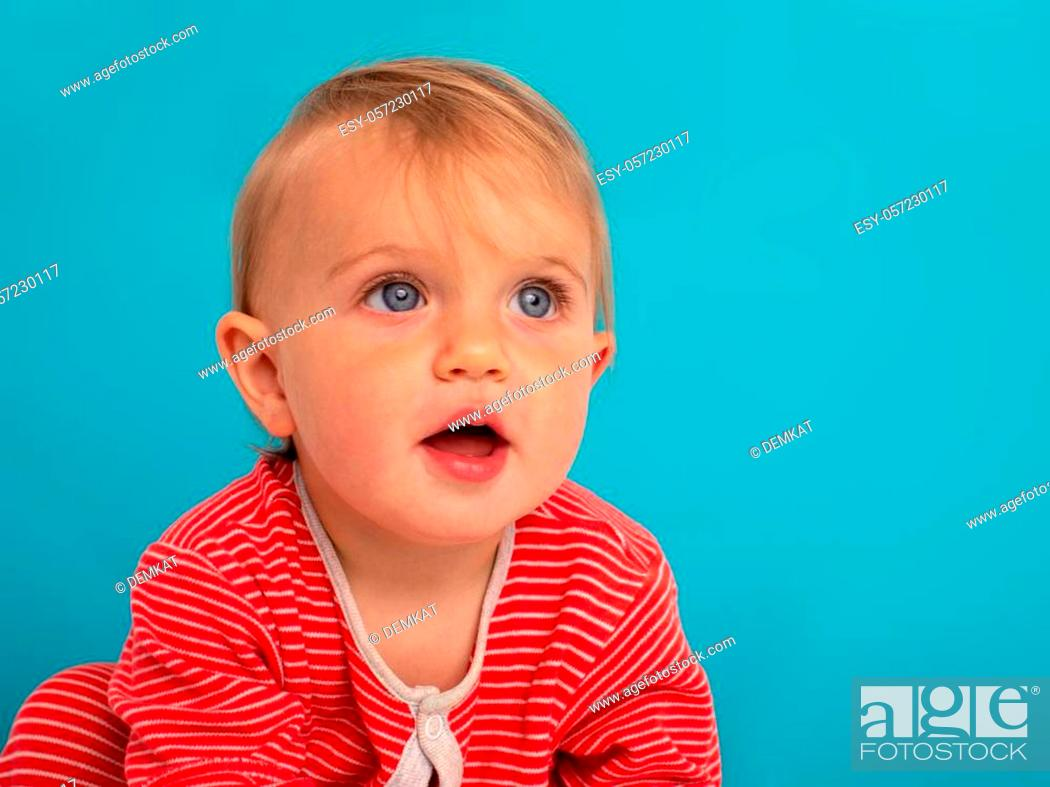 Stock Photo: Portrait of a little 11 month old girl smiling on a blue background.