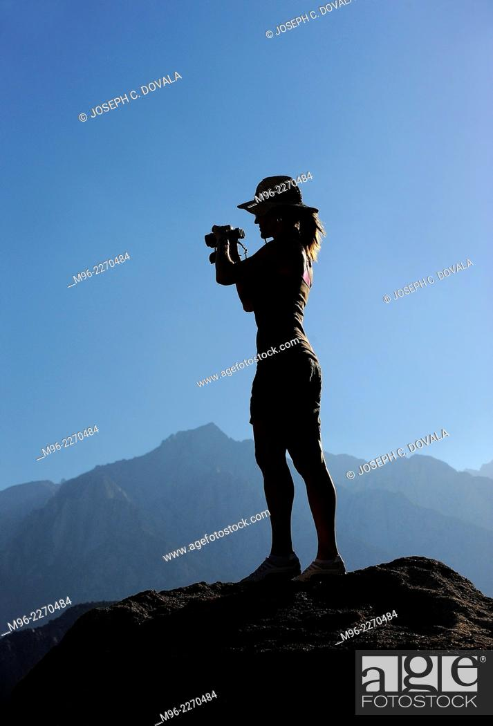 Stock Photo: Woman standing on rock with binoculars, Alabama Hills, California, USA.