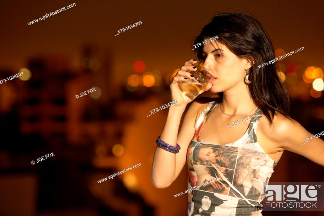 Stock Photo: young hispanic latin woman drinking glass of beer looking sad in buenos aires argentina.