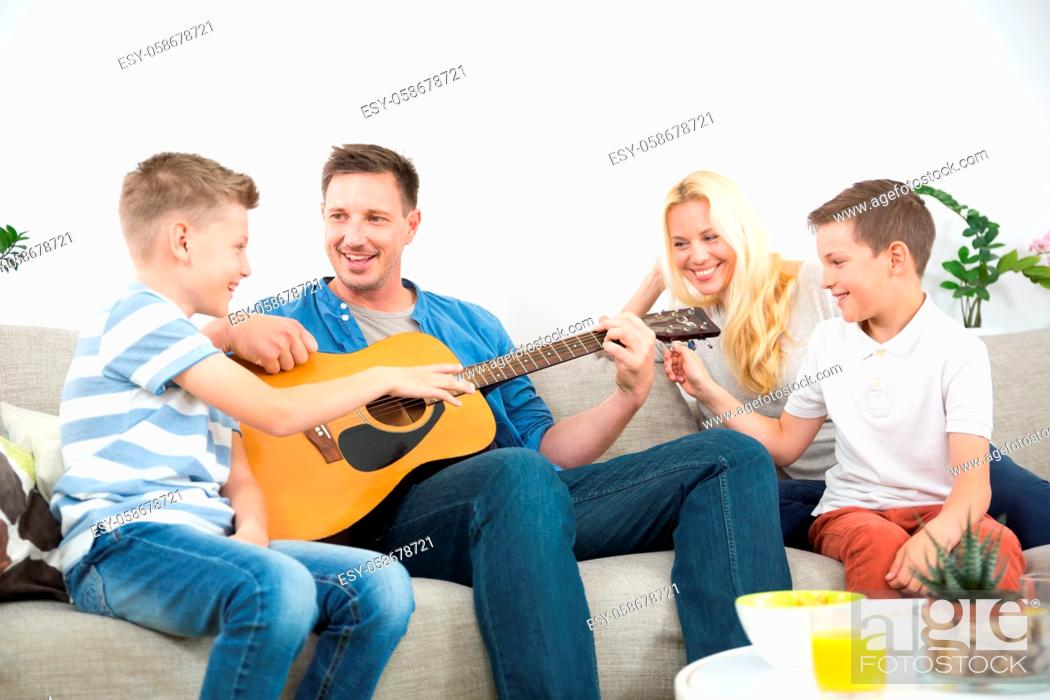 Stock Photo: Happy caucasian family smiling while playing guitar and singing songs together at cosy modern home. Spending quality leisure time with children and family.
