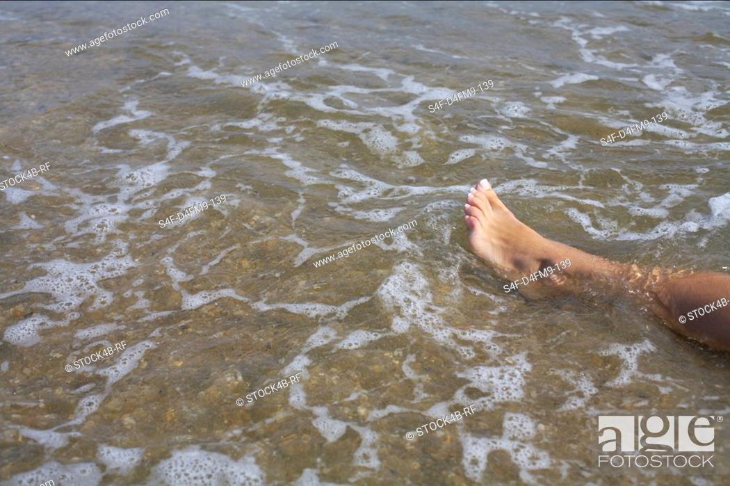 Stock Photo: Naked leg of a young woman in the shallow water of the sea, high angle view.
