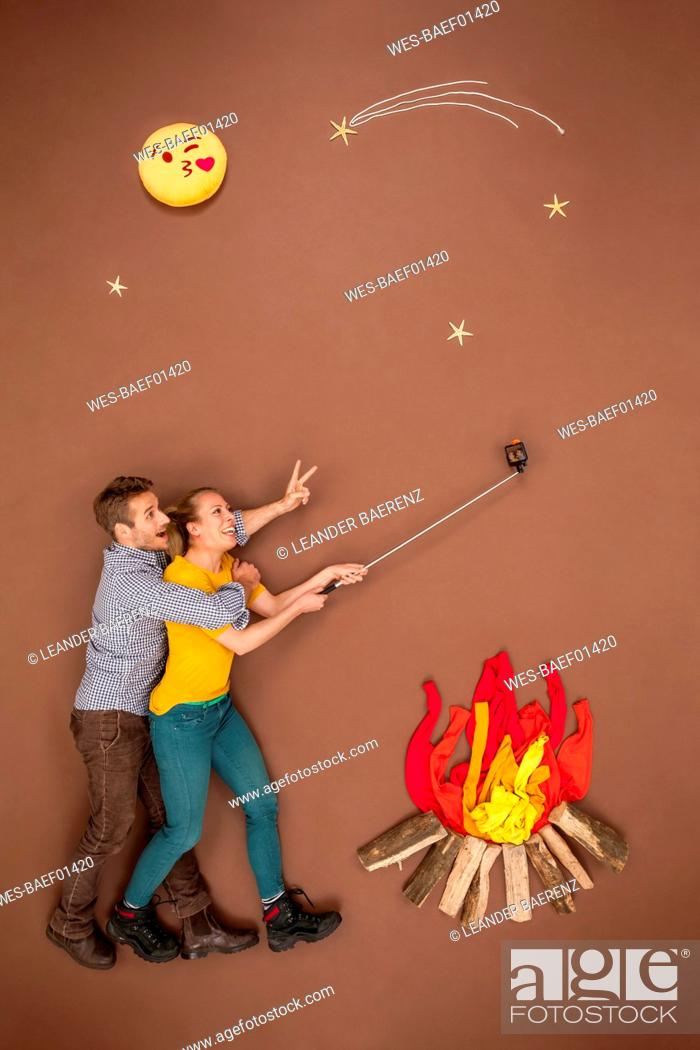 Stock Photo: Couple roasting sausages at the campfire and taking a selfie.