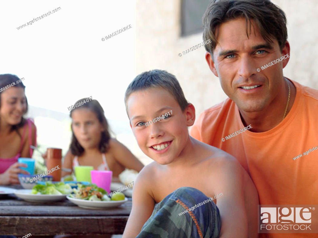Stock Photo: Father and son at meal outdoors.