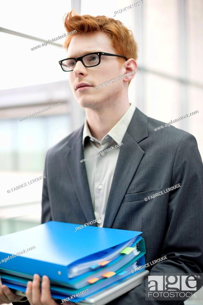 Stock Photo: Businessman holding files in an office.