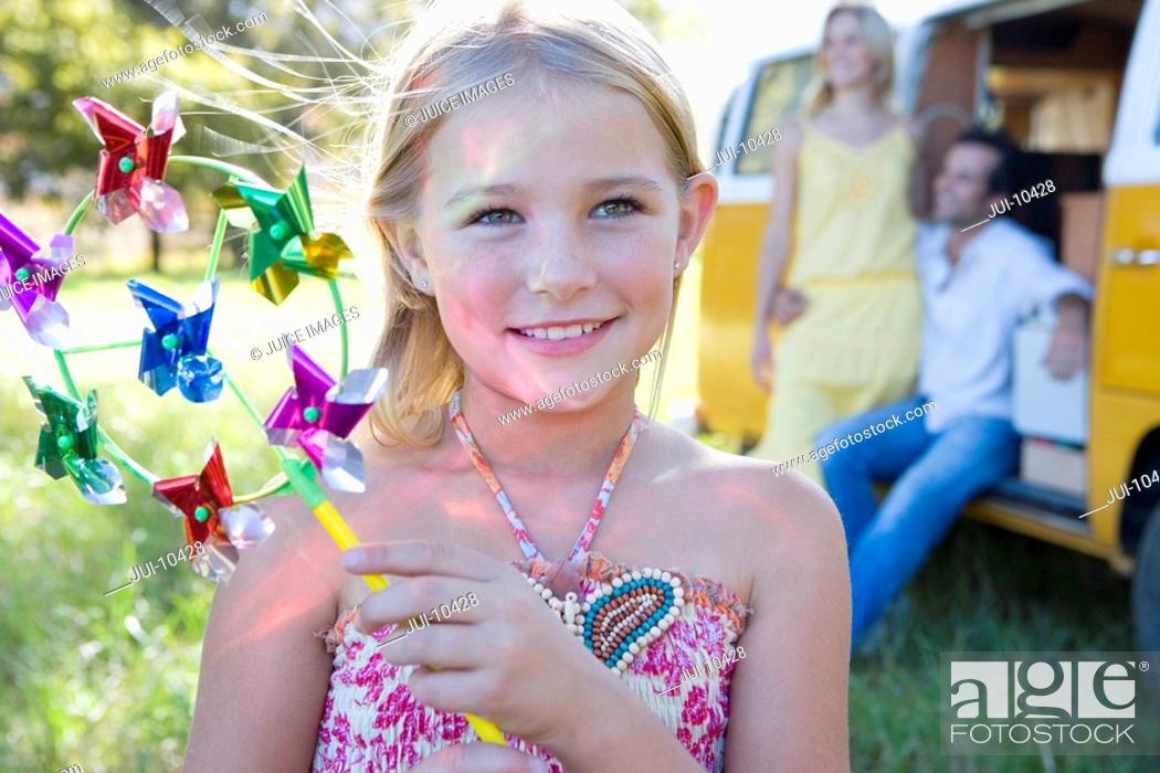 Stock Photo: Girl 5-7 with pinwheel, parents by camper van in background, smiling.