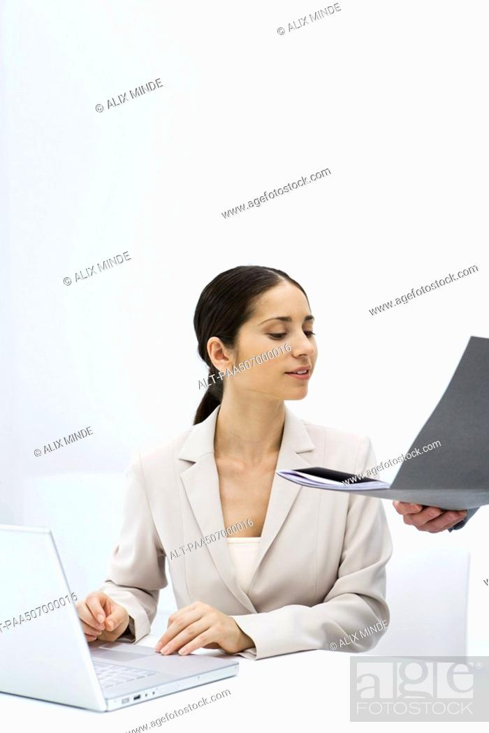 Stock Photo: Woman looking at a folder being held open for her, using laptop computer.
