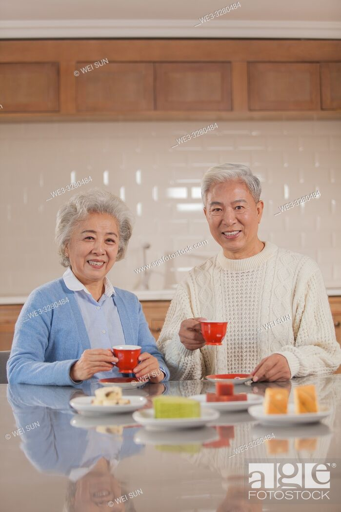 Stock Photo: Happy old couple drinking tea in the kitchen, Chinese ethnicity.