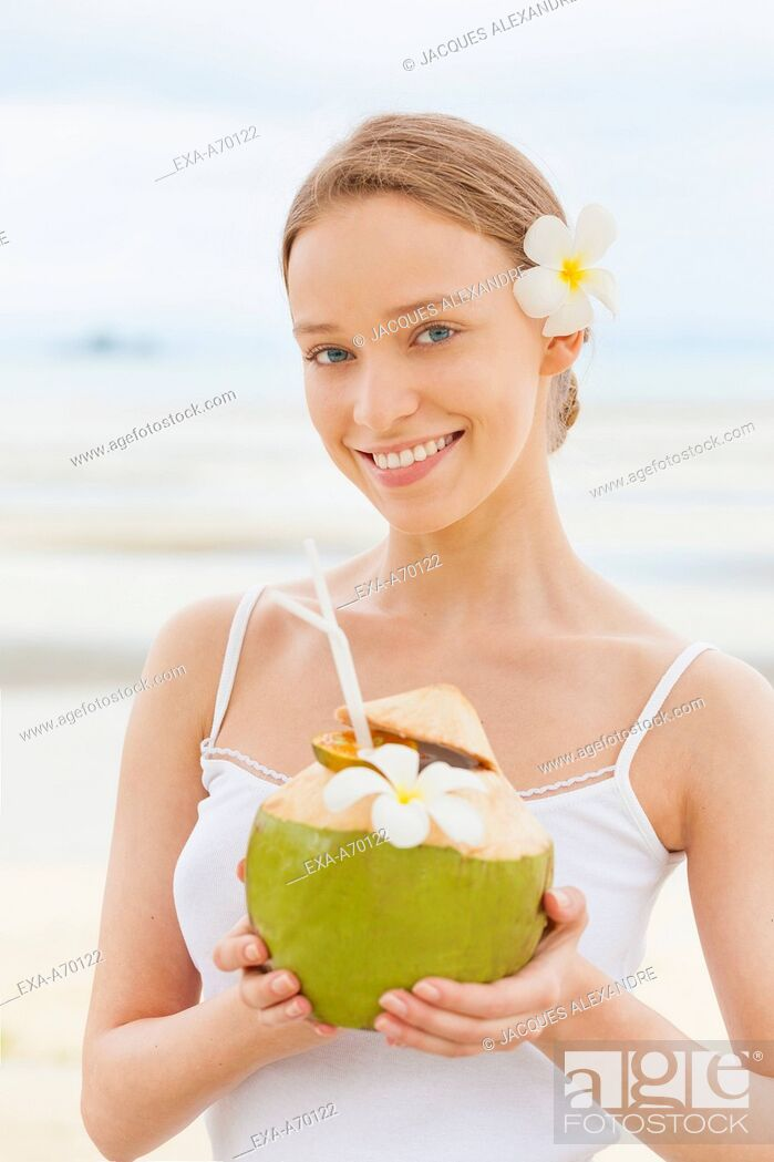 Imagen: Woman drinking from a coconut.