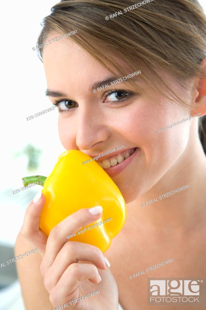 Stock Photo: young woman smelling yellow paprika.