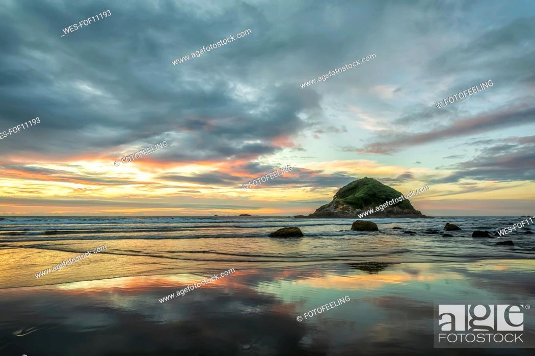 Stock Photo: New Zealand, Tongaporutu, Cloudy sky over sandy coastal beach at dusk with Motuotamatea island in background.