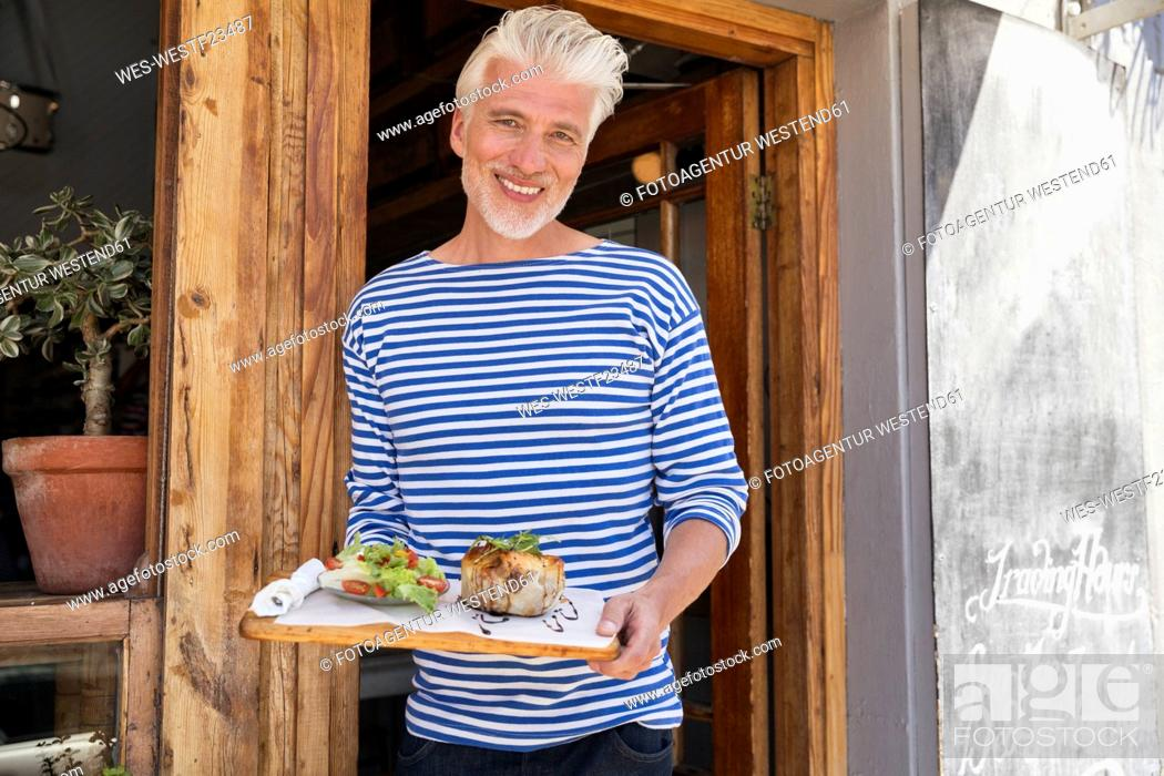 Stock Photo: Mature man standing in front of his restaurant, serving a dish.
