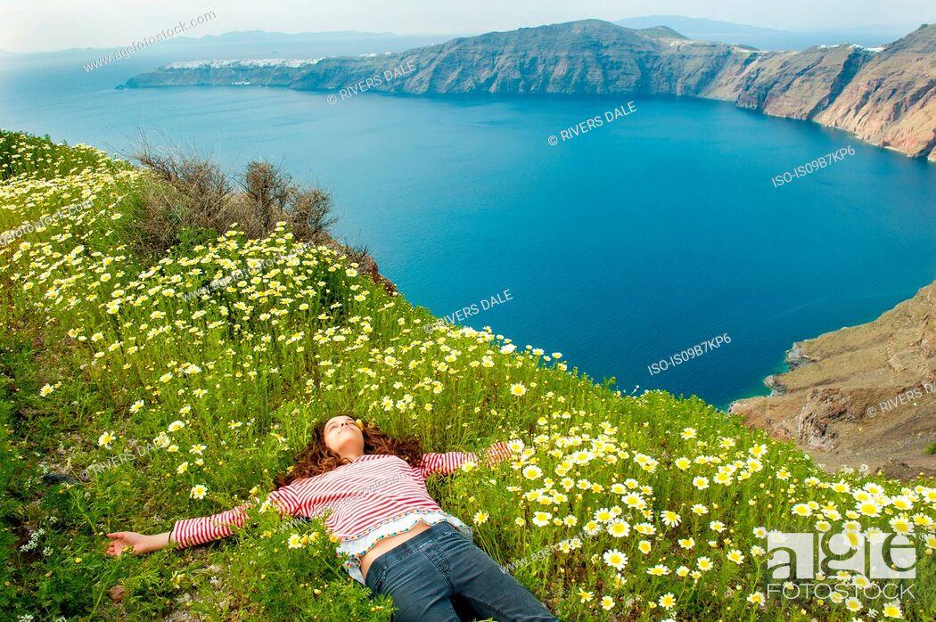 Stock Photo: Girl asleep on bed of flowers, Oía, Santorini, Kikladhes, Greece.