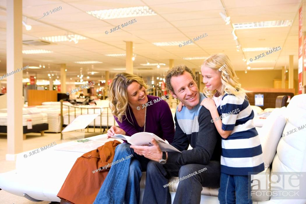 Stock Photo: Family of three in furniture shop, parents smiling at daughter 6-8.