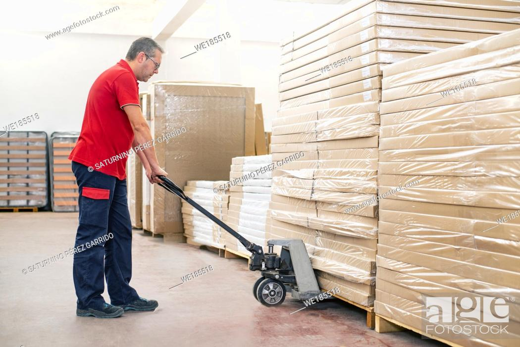 Stock Photo: Warehouse clerk handling products by means of a pallet truck.