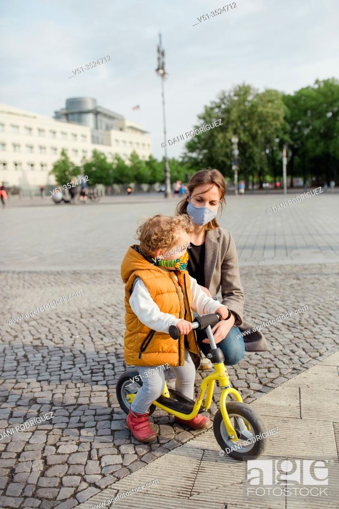 Stock Photo: Little boy 2-3 years old with mask and bicycle in Berlin.