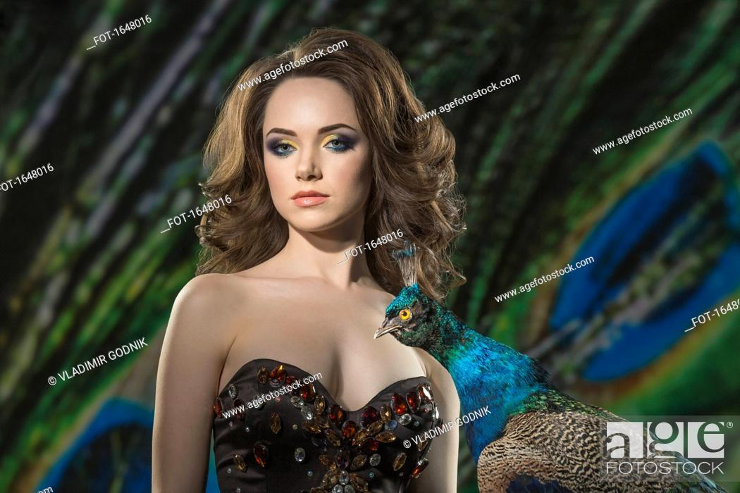 Imagen: Portrait of beautiful woman by peacock against feathers.