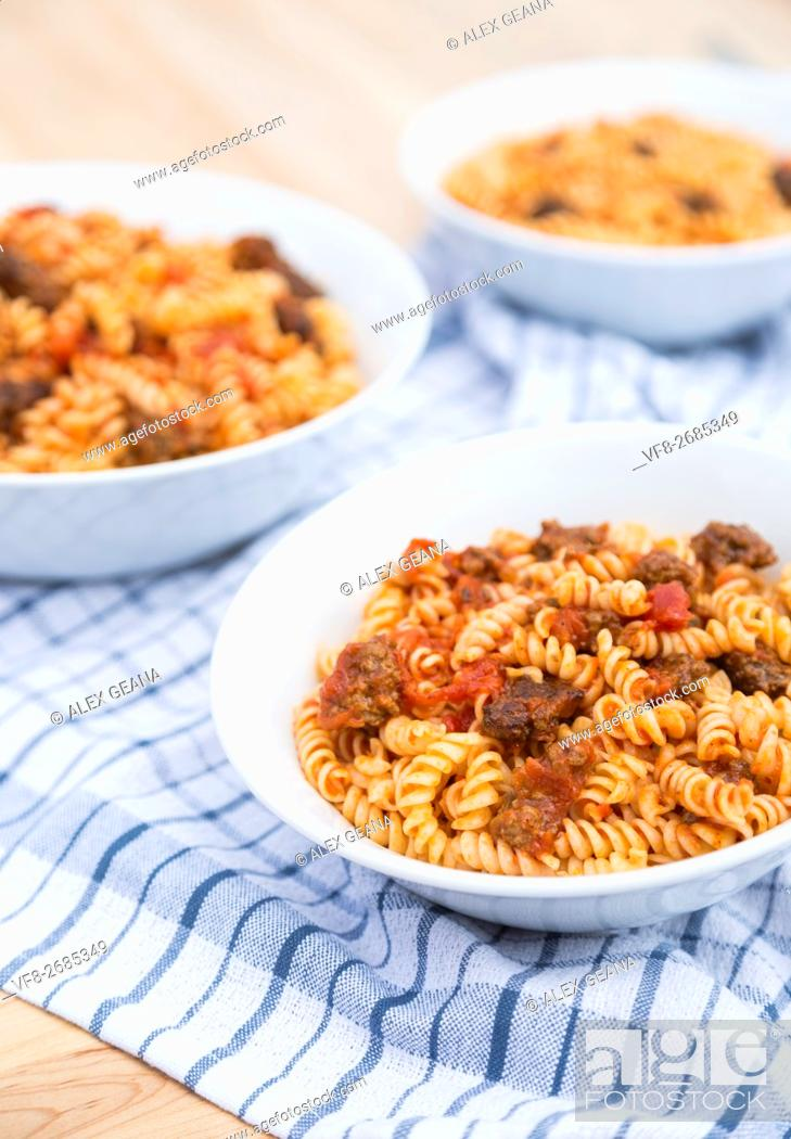 Stock Photo: Three bowls of Fusilli pasta, with a tomato meat suace, in white bowls on wodden cutting boards and on a blue checkered napkin.