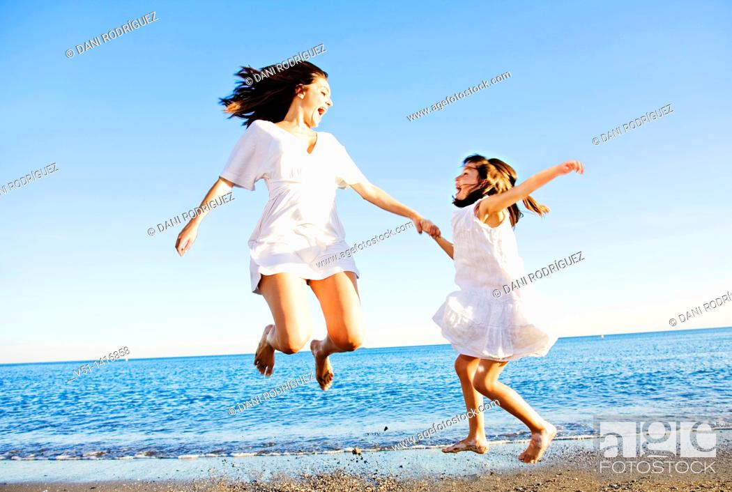 Stock Photo: Mother and daughter jumping and having fun at the beach.
