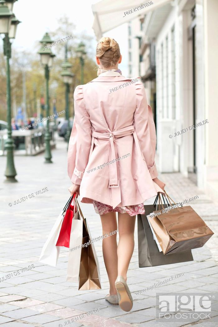 Stock Photo: Rear view of a woman carrying shopping bags.