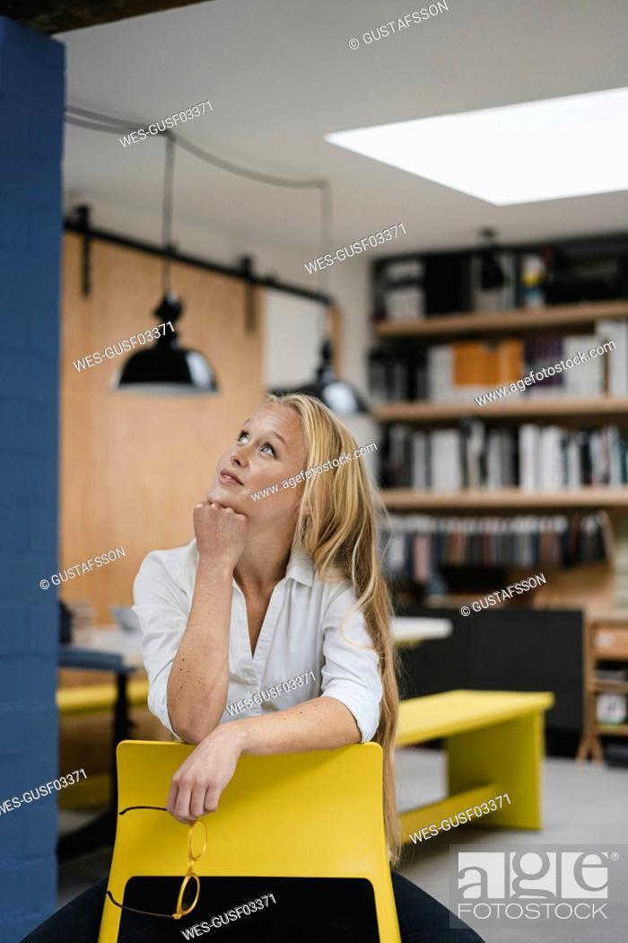 Stock Photo: Smiling young businesswoman sitting on a chair in loft office looking up.