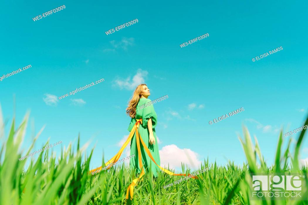 Photo de stock: Young woman wearing a green dress standing in a field with ribbons wrapped around her waist.