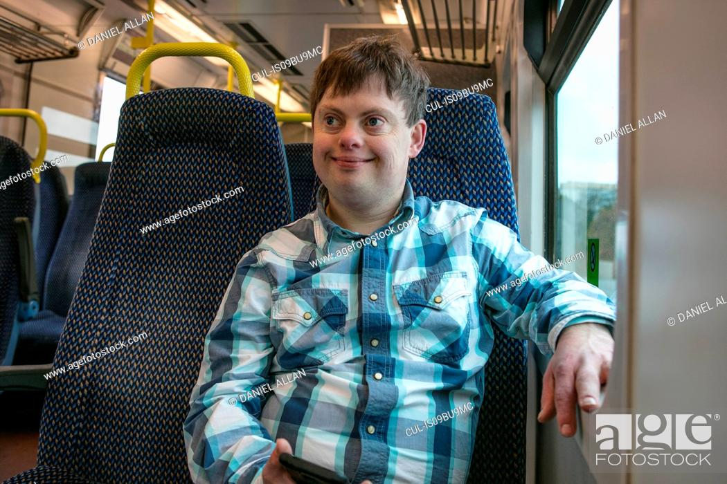Stock Photo: Man with down syndrome with cell phone on train.