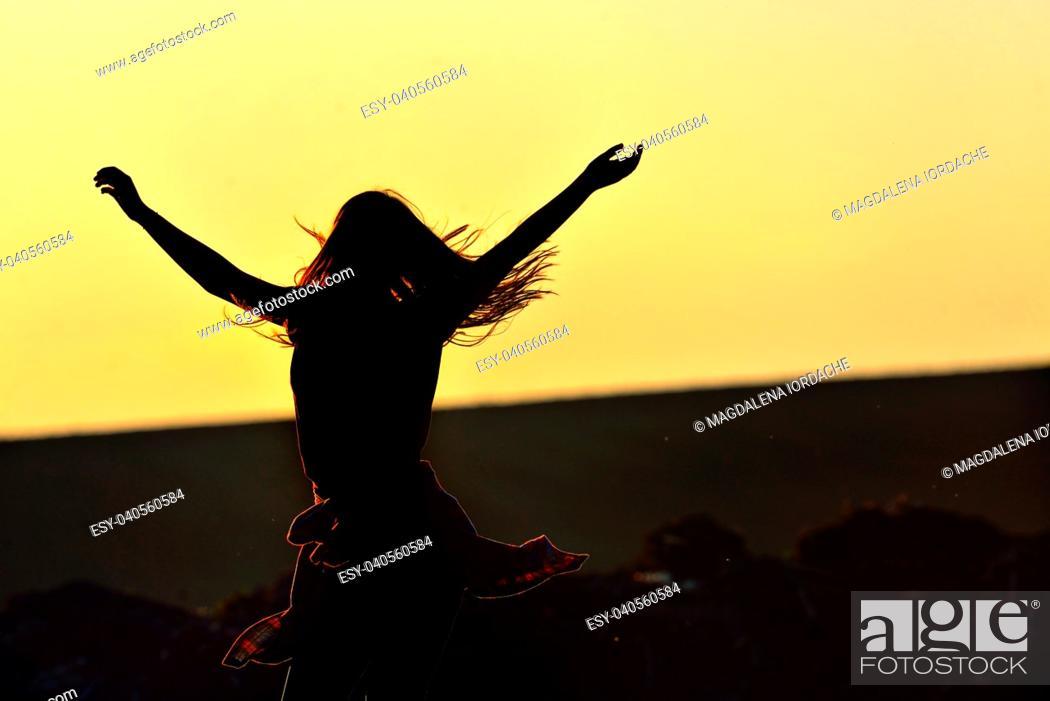 Stock Photo: Teen girl jump against beautiful sunset on field.