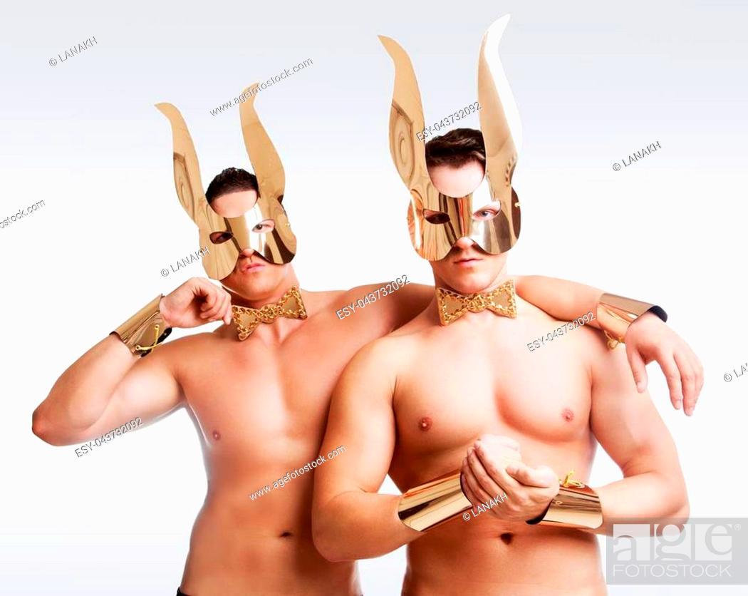 Imagen: striptease dancers wearing golden rabbit ears in the studio isolated against white background.
