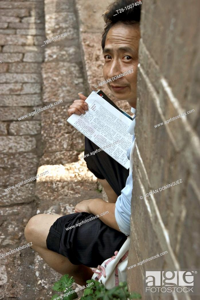 Stock Photo: a man reads, sitting in the street. China.