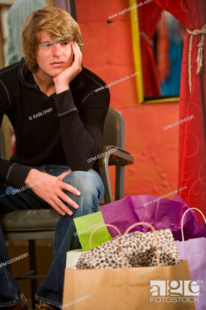 Imagen: Bored young man sitting by shopping bag.