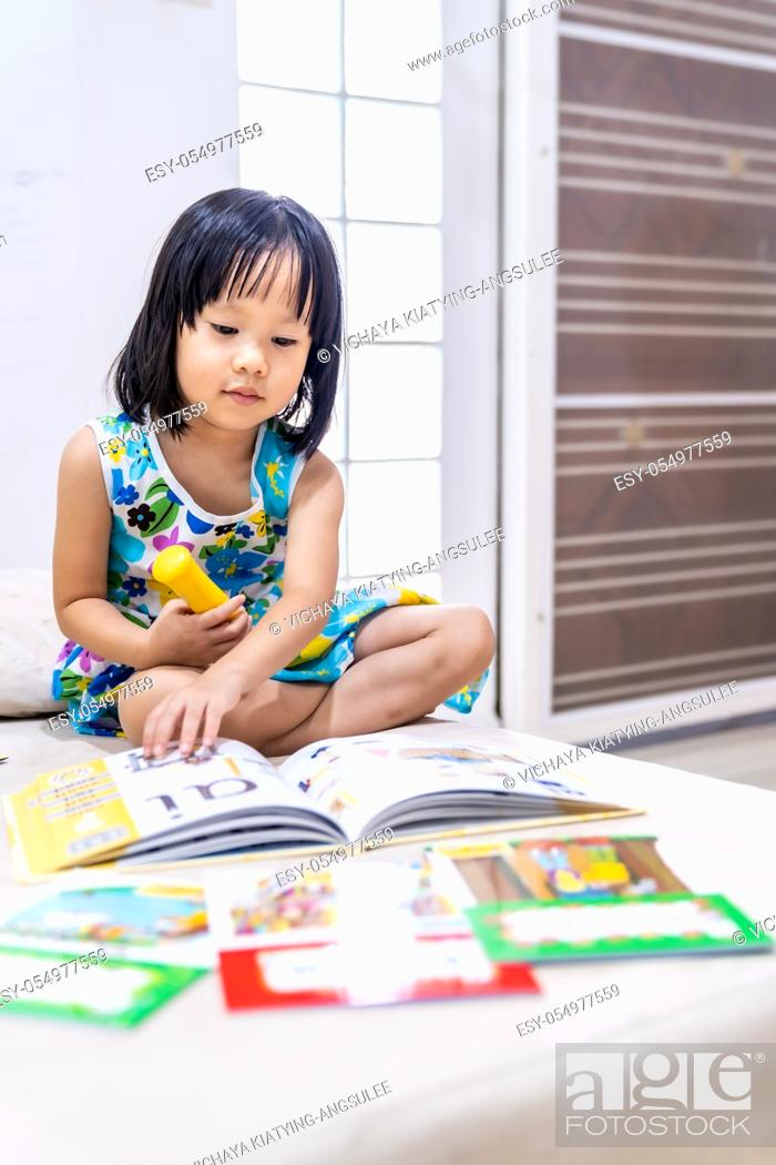 Stock Photo: Asian girl child reading interactive book in living room at home as home schooling while city lockdown because of covid-19 pandemic across the world.