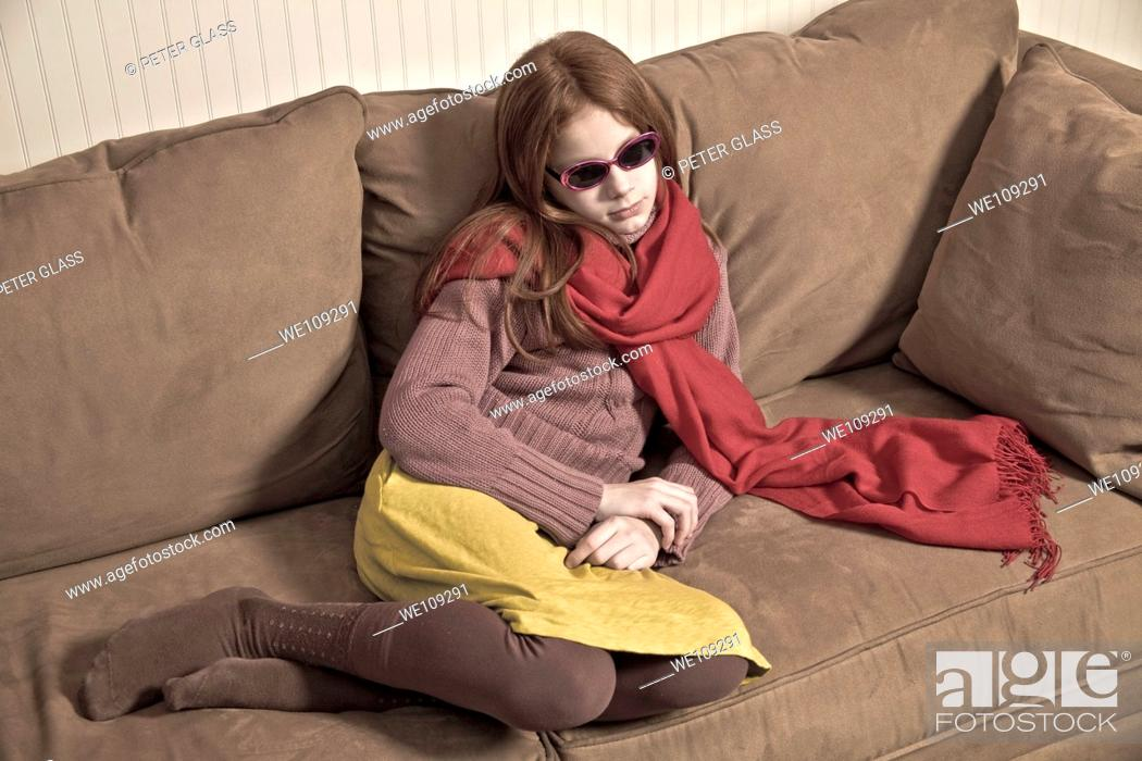 Stock Photo: Preteen redhead girl wearing sunglasses and a long scarf.