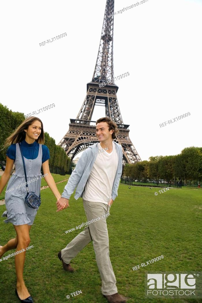 Stock Photo: Young couple walking in park with Eiffel tower in background, Paris, France.