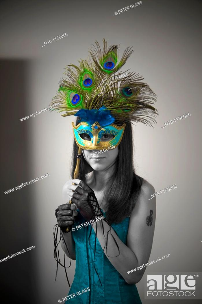 Stock Photo: Young woman holding a mask over her face.