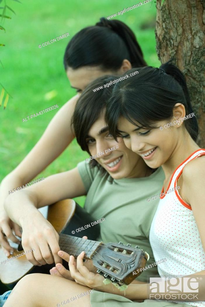 Stock Photo: Group of young friends sitting by tree with guitar.