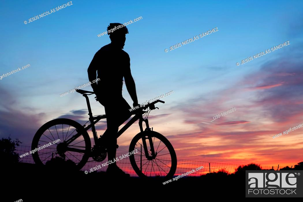 Stock Photo: Mountain bike rider resting at dusk.