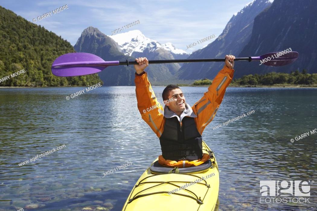 Stock Photo: Man hoisting oar of kayak over head in mountain lake.